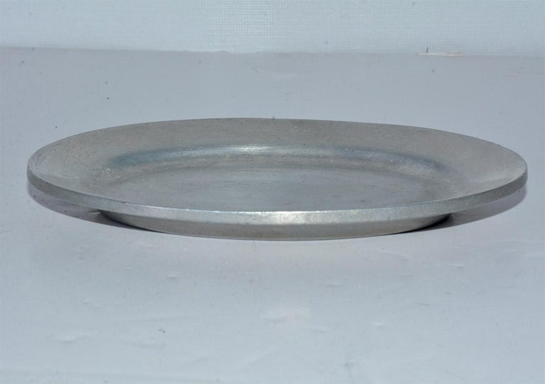 The vintage pewter platter, replicating 18th century American pewter ware, is oval in shape and has a raised rim. Stamped on the bottom is