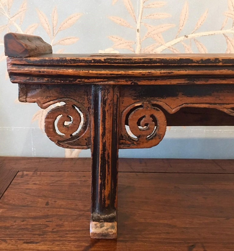 A small mid-19th century wooden altar table with worn black lacquer finish, cloud spandrels at tops of legs, and decorative apron.