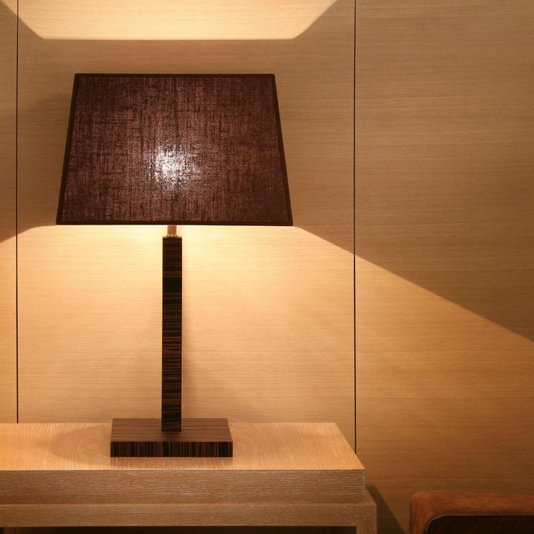 Playful geometry and timeless materials come together in the woody table lamp. Square from top to bottom, the lamp's base and stem are made in oak with your choice of a wenge varnish or Makassar ebony veneer. The lampshade, in an original shape, is