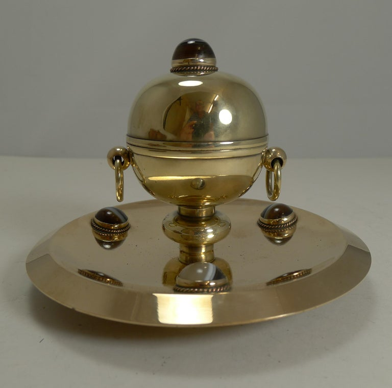 A handsome Victorian English inkwell made from a combination of polished bronze (base) and brass (spherical inkwell). The metals have been professionally polished to gleam showcasing the four polished cabochon agate stones. There is a ring handle to