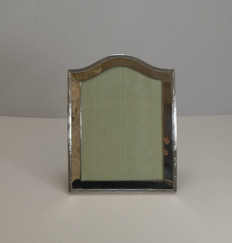 A very handsome and elegant photograph frame made from English sterling silver and a solid oak backing.  Lovely quality, the silver wraps around the sides with a decorative raised border outlining the simple, smart shape.  The silver is fully