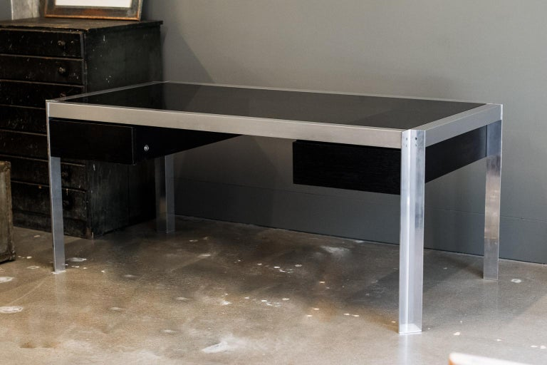 Inspired after meeting renowned architect and designer Le Corbusier, Georges Frydman founded his award-winning company E.F.A. in France in 1954. Executive desk with aluminum frame and dark stained wood drawer fronts, topped with smoked glass. France
