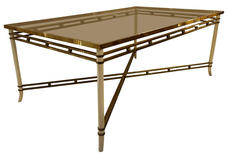 Midcentury French cream colored metal legs with brass details dining table. Smoked taupe glass top. Decorative small brass balls are placed along the apron as well as the cross stretcher of table. Glass top has minor scratches due to age and use.