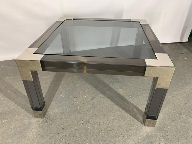 Heavy Lucite table by Jonathan Adler features chrome accents and glass top. Good condition with minor imperfections.