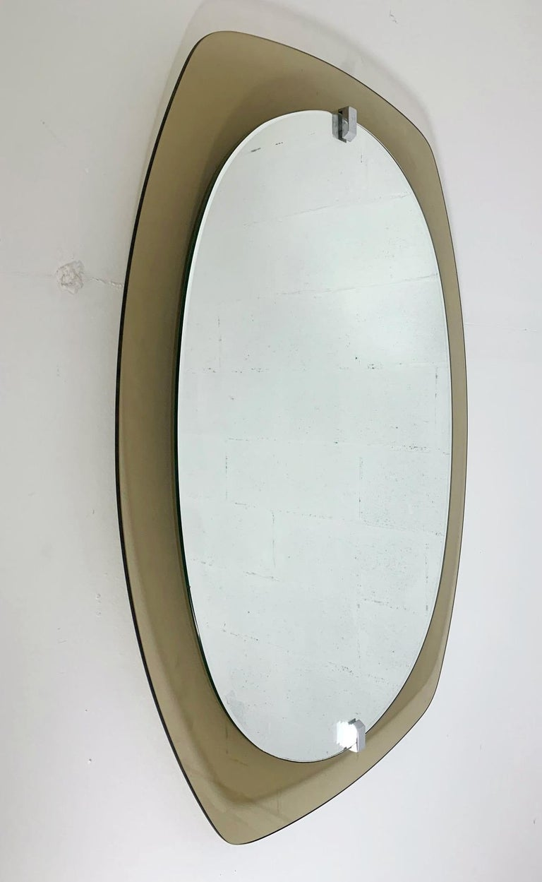 Vintage Italian oval mirror with smoky brown beveled glass by Veca / Made in Italy, circa 1960s Original sticker on the back Measures: Height 31.5 inches, width 23.5 inches, depth 2 inches 1 in stock in Italy Order reference #: FABIOLTD F66