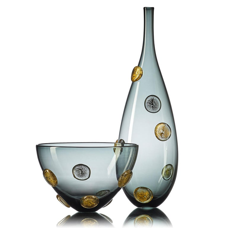 A luminous statement in translucent grey hand blown glass, the moneto vessel with gold dots features a Cascade of raised metallic coin-shaped dots, encased in clear glass. This large-scale designer vase is hand blown from start to finish by Vetro