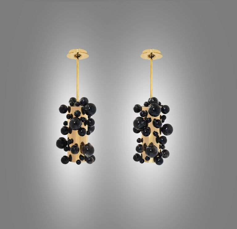 Pair of smoky rock crystal bubble pendant lights with polished brass finishes. Created by Phoenix Gallery, NYC. Two sockets installed each light. Use LED warm light bulbs. 50w each. 100 w total. Dimension of the pendant: 8