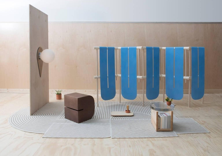 A large screen composed of solid wood posts with hand-cut hinges and bronze sheet. The form evokes prayer flags or a snaking river. The blue color of the bronze is achieved through a custom patination process.   As each screen is made to order,