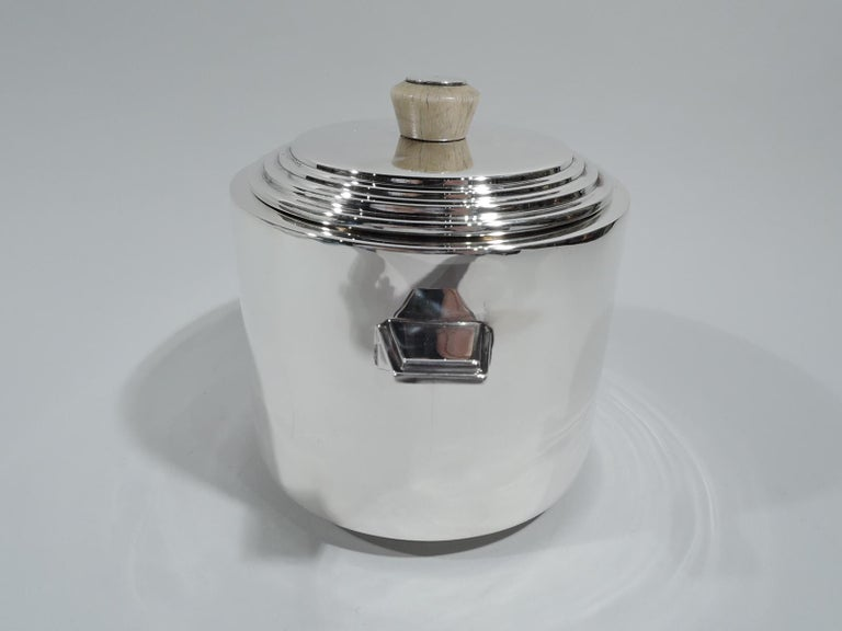 George V sterling silver ice bucket. Made by Hollings & Hitchinson in Birmingham in 1933. Straight sides with stepped L-form tab handles. Cover stepped with round and tapering wood finial. Snazzy Art Deco from across the Atlantic. Fully marked