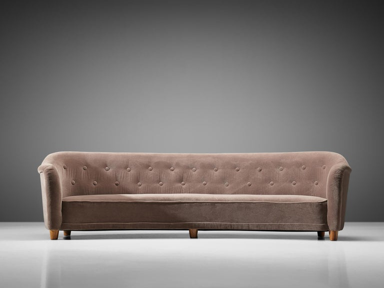 Large curved sofa, possibly by Greta Magnusson-Grossman for Studio, wood and fabric,  Sweden, circa 1938.  This rare sofa, upholstered in a mauve velvet fabric was produced circa 1938. The design is attributed to designer Greta Magnusson-Grossman