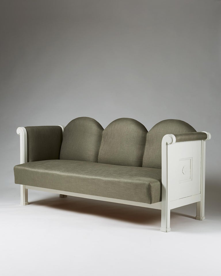 White painted wood, newly upholstered in linen fabric.  Measures: L 195 cm/ 6' 5 1/4'' H 86 cm/ 2' 10'' D 88 cm/ 2' 11''  Custom order from Eliel Saarinen to Munksnäs hotel, Finland. These models only produced for the hotel.