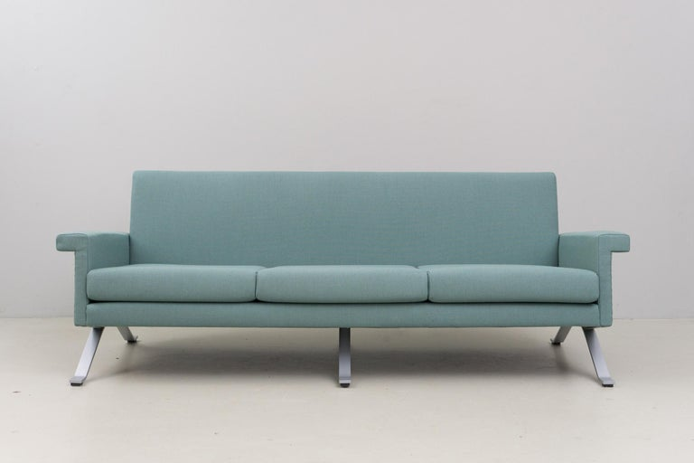 This minimalistic and elegant three-seater sofa has a matt chromed metal structure and new upholstery and cover. The cover is made of 100% wool in a cool grayish green. Excellent condition.  The last production of this piece was manufactured in