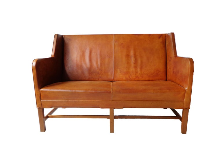 Two-seater sofa model 5011 in original cognac leather and six-legged mahogany base. Produced by Rud. Rasmussen Cabinetmakers, Denmark. Minor marks on the frame, patina to the leather. Back covered in original canvas.