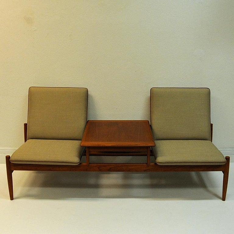 Special and rare midcentury sofa set named Saga- including a teaktable that can be removed and placed where you wish.New upholstery in beige soft fabric. Leather piping around the seatedges. Teaklegs and trunk. This set is designed by Gunnar Sørlie