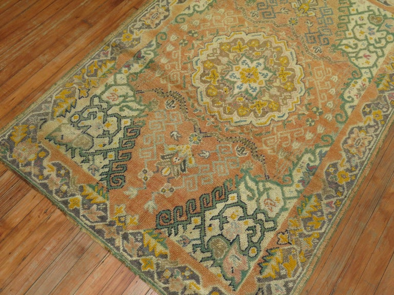 A early 20th century antique Turkish Oushak rug in predominant orange accents.