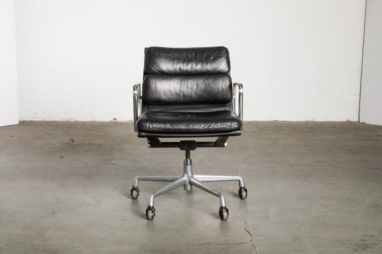 This sought after and in-demand black leather desk chair is the classic 'Soft Pad Management Chair' from the aluminum group line, designed by Charles and Ray Eames for Herman Miller. Featuring the original vintage black leather upholstery over