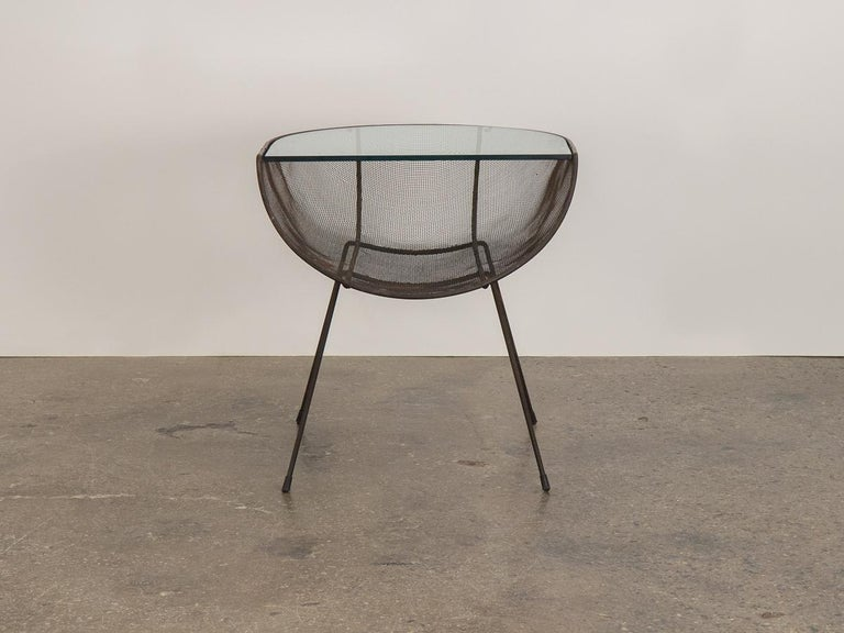 Seldom seen metal side table designed by Sol Bloom for New Dimensions. Incorporated expanded metal catch-all floats on splayed iron rod base. Original glass tabletop is very clean and with no chips and minimal surface scratching. In nice condition,