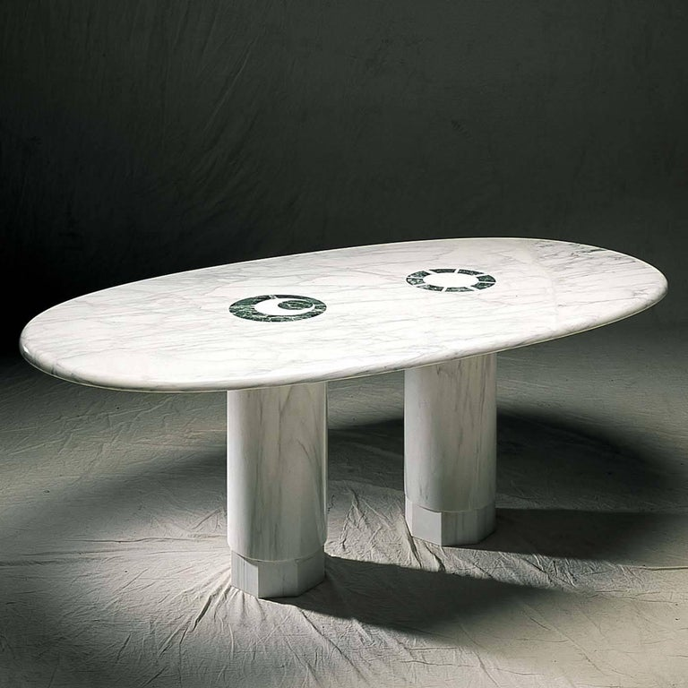 A timeless design by Adolfo Natalini for a dining table that combines classic materials with modern silhouette. The entire structure is made of Carrara marble and features a stunning oval top resting on two smooth pillar-shaped supports with an