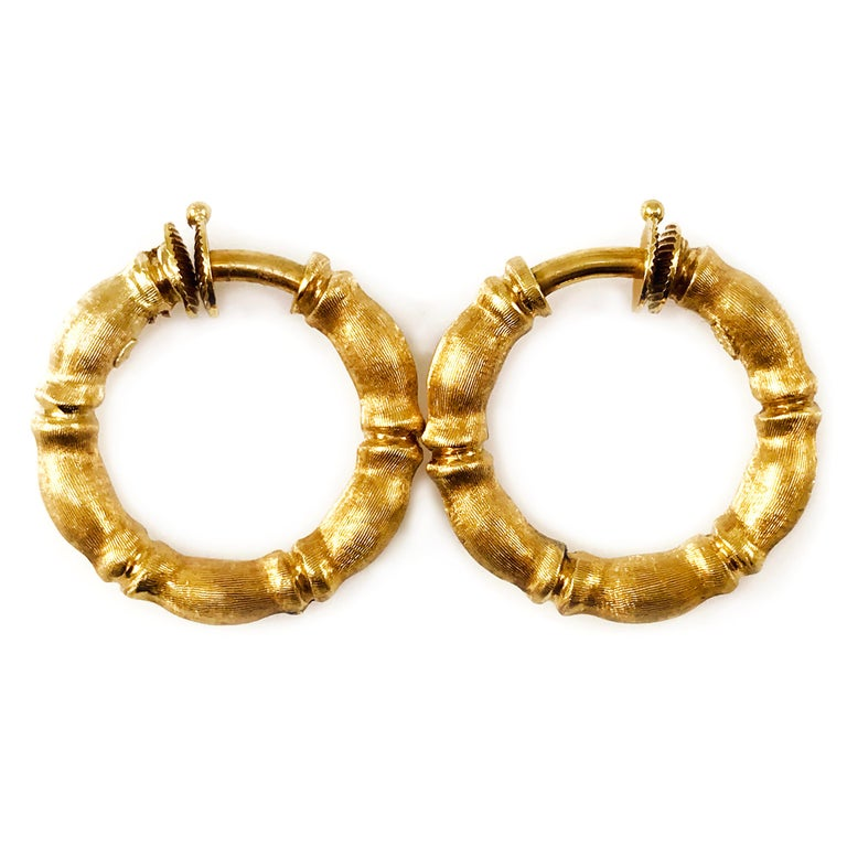 Solid 18 Karat Bamboo Gold Hoop Earrings with a brushed satin finish. These unique earrings are not for pierced ears as they have no post and springs closure clip. The total gold weight of this earrings is 13.8 grams.