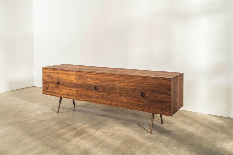 This special edition sideboard with solid brass underframe has six drawers and is made in solid walnut with an oiled finish.   It has traditional finger jointing detail on the top and bottom edges and carefully considered detailing for the drawer