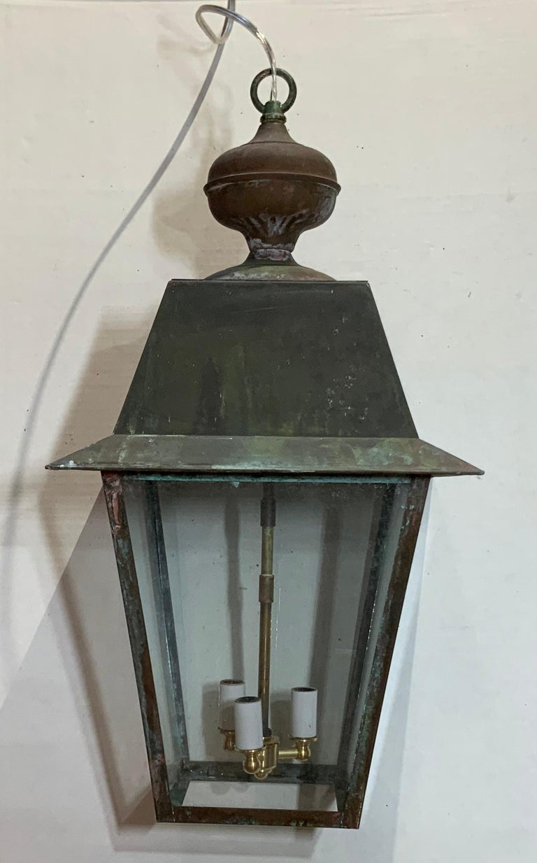 Four sides hanging Lantern made of solid brass with three 60/watt lights, newly rewired. Brass canopy included.