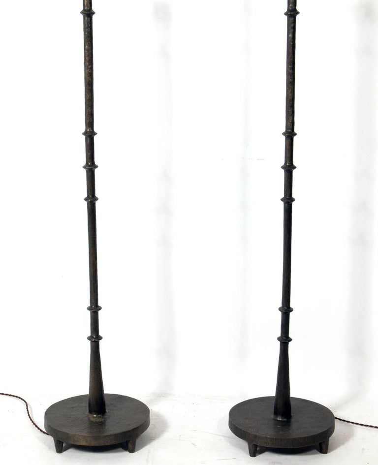 Solid bronze floor lamps by Tom Corbin, American, circa 2000s. They retain their warm original patina. Signed and dated at the bases. Corbin's work was clearly influenced by Diego Giacometti. The lamps have been rewired with cloth cords and the