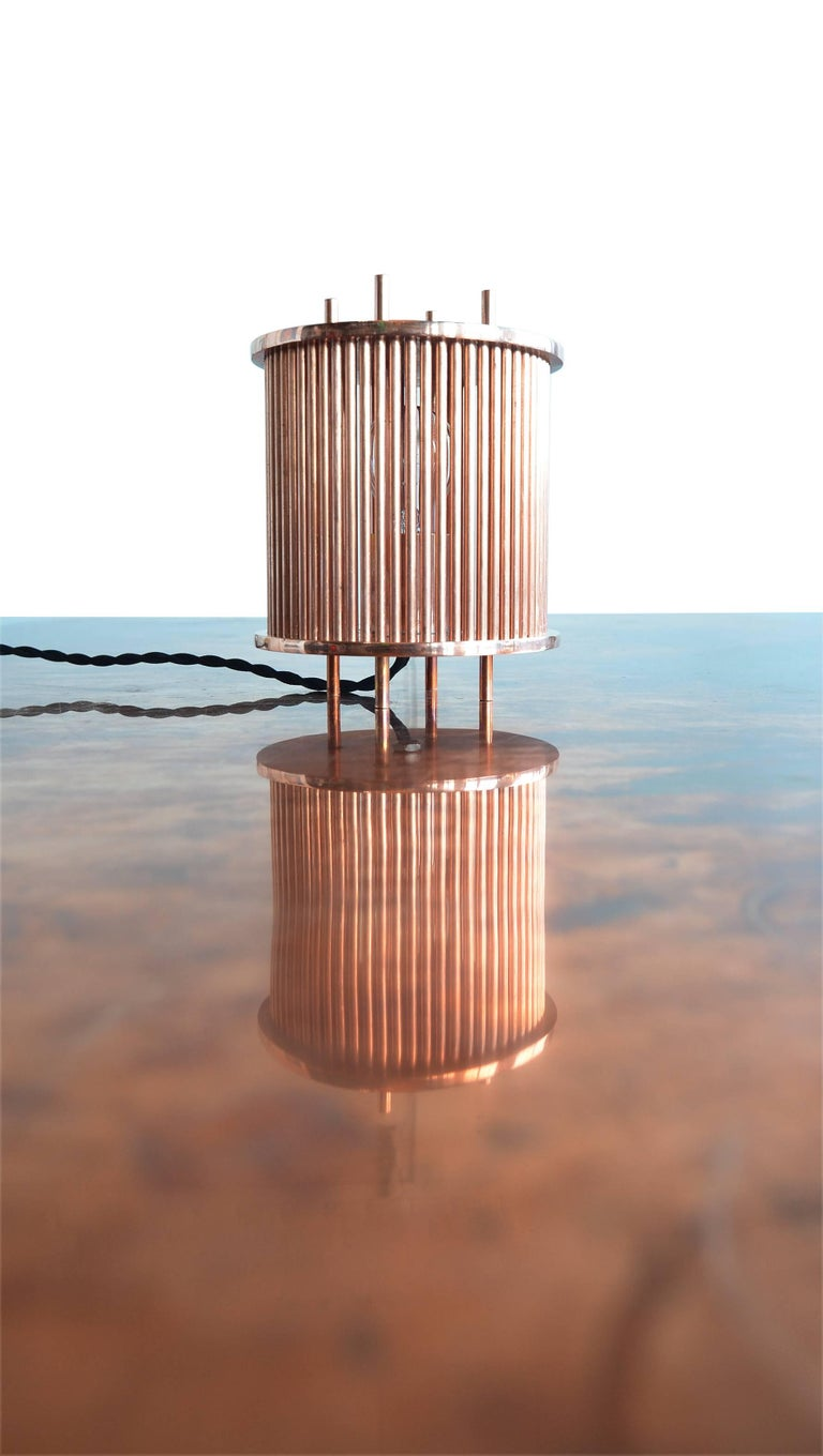 An incredible, bright solid copper table lamp by Porch Modern.   These lamps are created from solid plate copper and rod. Milled inset holes holding 63 individual solid copper rods.  Lit with a single raw build which produces incredible shadows