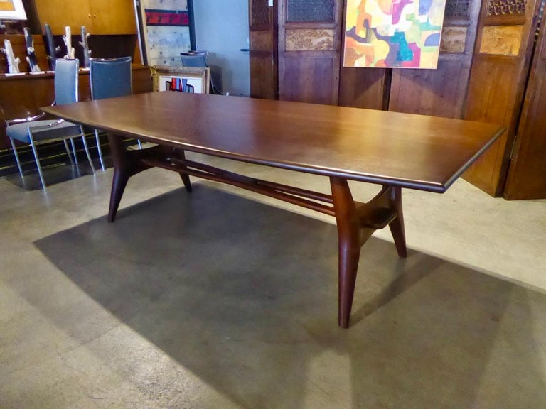 A solid mahogany dining table attributed to Monteverdi-Young, circa 1950s. The top is a curved rectangle and the spectacular base is distinguished by an over-scale Hans Wegner style wishbone stretcher that resolves as a through-tenon. The table has