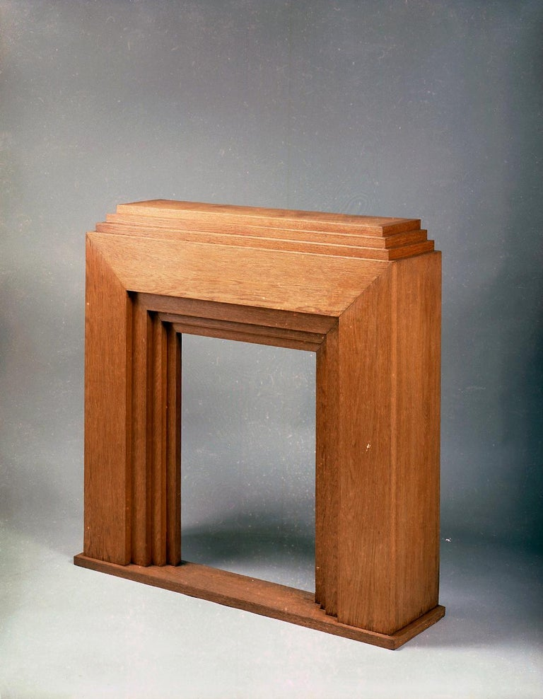 Solid oak mantelpiece with stepped top and stepped fireplace. The whole raised on a rectangular base. Provenance: Former collection of Mrs Madeleine Vionnet.