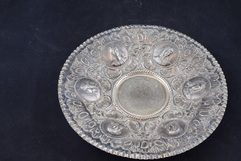 Circular silver tray embossed in its color, circular and decorated on the edge with a series of busts inside pearl strings, accompanied by scrolls, plant elements and motifs of clear Rococo memory, which has a jagged edge to the outside. The piece