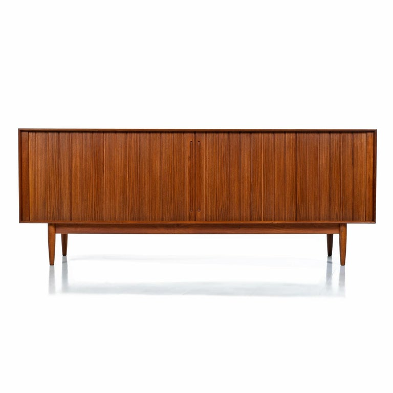Mid-Century Modern Johannes Aasbjerg solid teak sideboard credenza. Made from 100% solid teak (except for the interior shelves), this sideboard is a perfect marriage of design and function, featuring exquisite craftsmanship, a finished back and lots