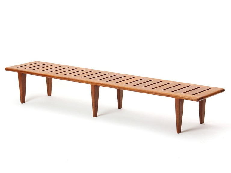 A midcentury solid teak bench with a slatted seat over six (6) tapered legs. Designed by Hans Wegner and made by Johannes Hansen in Denmark, 1950s.