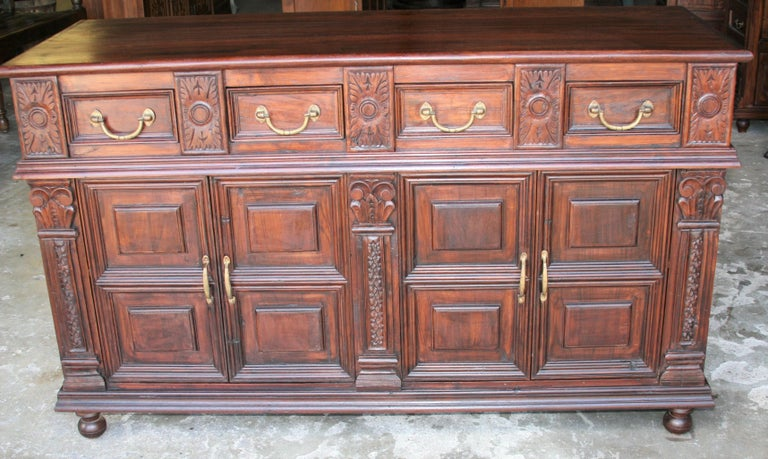 An unique custom made solid teak wood credenza from a French Colonial home in Asia. It has four upper drawers and two large bottom shelves. It is mounted on ball feet. It retains original hand cast brass hardware. It comes from a town Pondicherry in