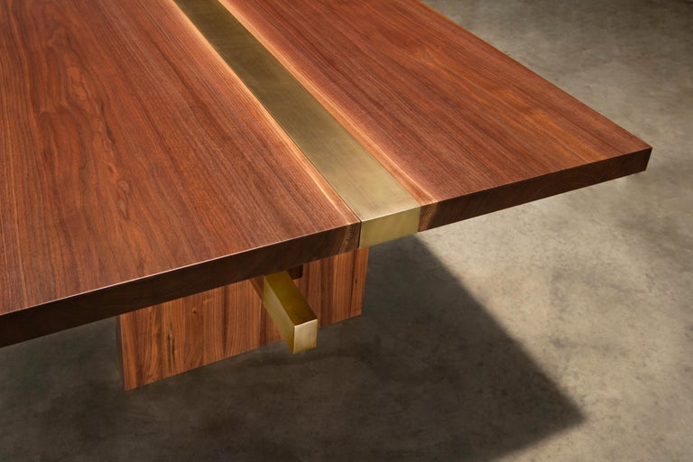 The Dequindre dining table uses two solid walnut slabs jointed to a brass metal insert to compliment the colors of each material. The solid walnut legs are also capped with brass as well to keep the style of the table constant throughout.   This