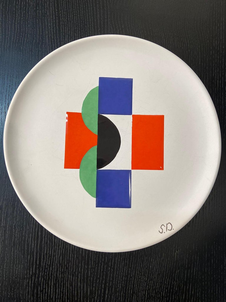 Sonia Delaunay, set of 6 plates and 1 large plate, circa 1985 Edition Moustiers France & Artcurial, Paris Signed with the initials S.D on the border of the plates White ceramic with abstract central decoration enameled polychrome Measures: