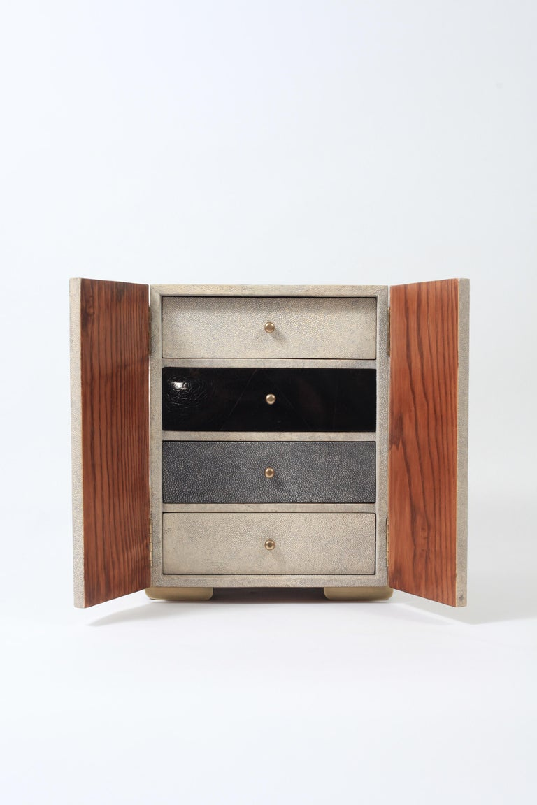 The Sonia jewelry chest in cream shagreen, shell and brass by R&Y Augousti is a stunning piece to store your personal items. This piece has 2 doors that open to 4 drawer compartments, inlaid in a mixture of cream shagreen/black shell and grey blue