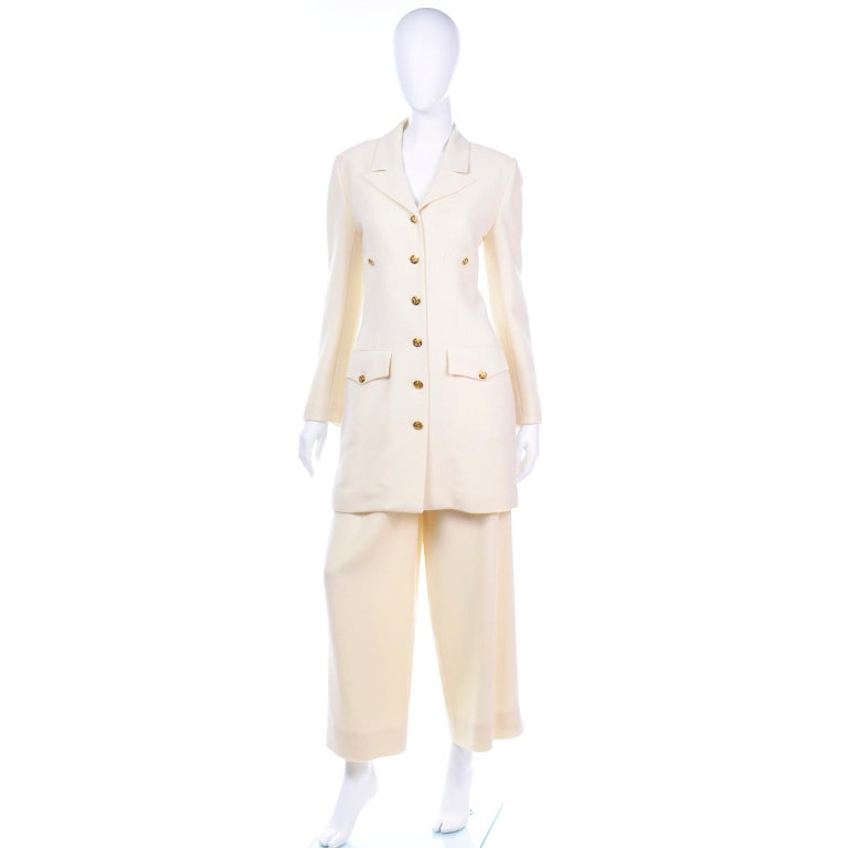 This is such a beautiful Sonia Rykiel ivory textured wool suit with a long line blazer and pleated wide leg trousers. The longline jacket has two functional buttoned breasted pockets and two flap pockets. The front of the jacket is secured with