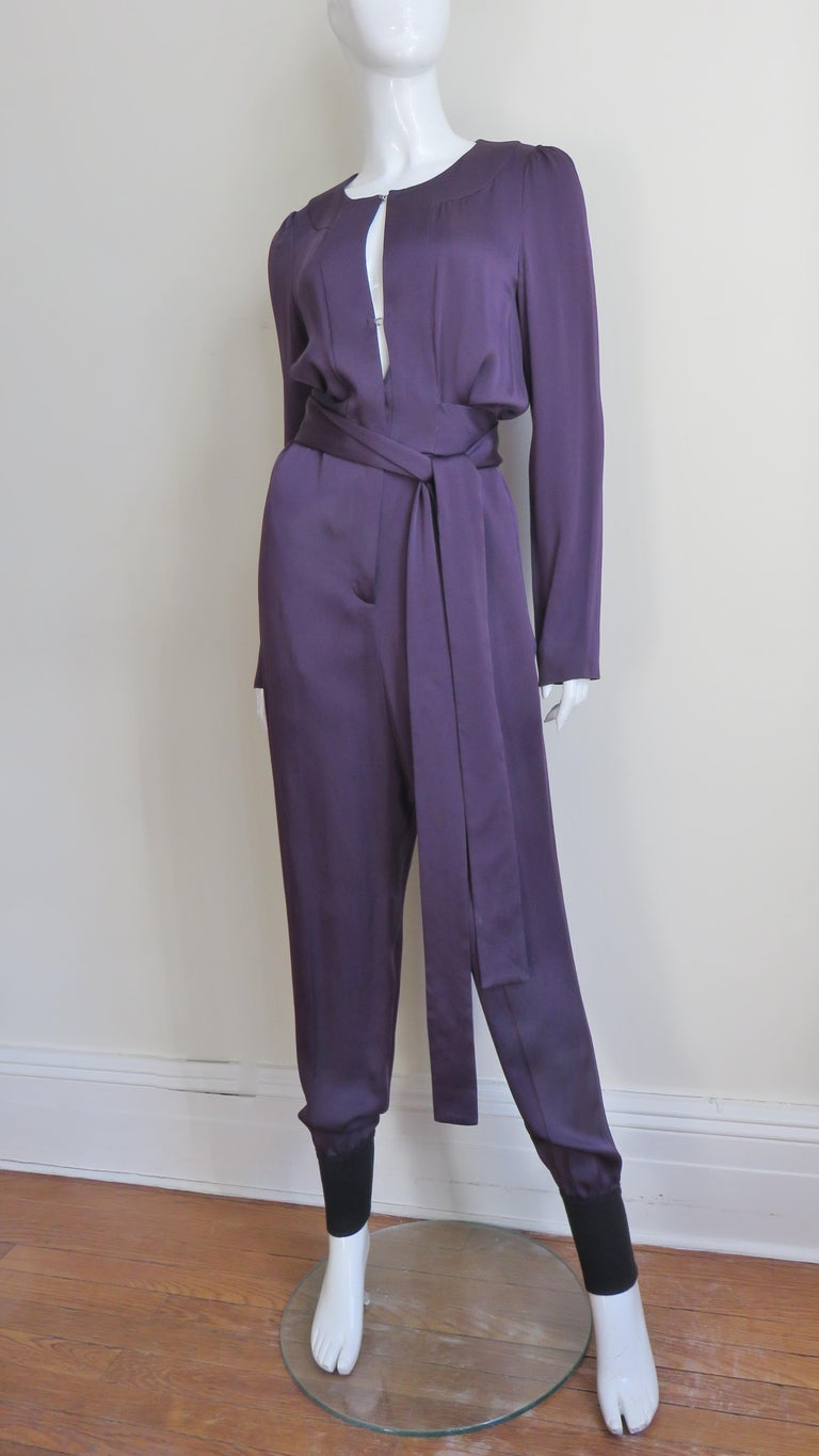 A fabulous eggplant purple silk jumpsuit from Sonia Rykiel.  The jumpsuit has long sleeves, cuffed full pant legs, hip side seam pockets and a long belt wrapping around the waist.  It has a keyhole front closing with several silver hooks revealing a