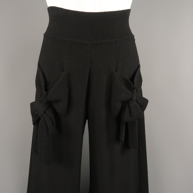 Vintage SONIA RYKIEL pants come in black virgin wool blend knit with a high rise, thick waistband, wide leg, ribbed stripe, and bow detailed pockets. Made in Italy.   Very Good Pre-Owned Condition. Original retail price: $550.00 Marked: FR 40
