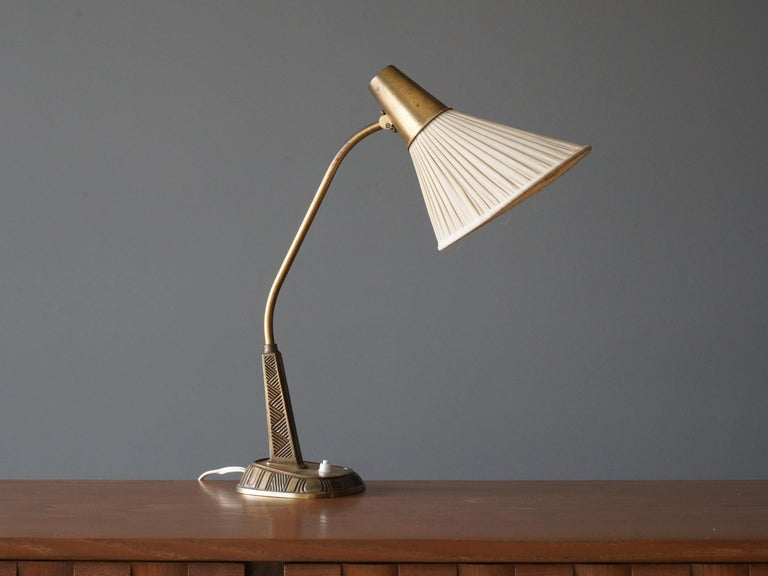 An adjustable table lamp / desk light. Designed by Swedish sculptor Sonja Katzin, (1919-2014). Produced by ASEA, Sweden, 1950s.  Executed in brass, original fabric screen.