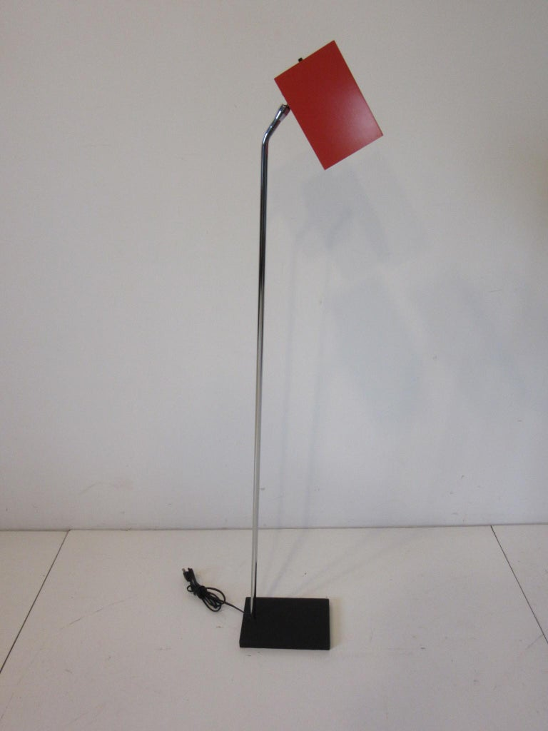 A well crafted floor lamp with heavy satin black steel base and chrome shaft having a medium orange adjustable metal box shade designed by Robert Sonneman for the George Kovacs Lighting Company.