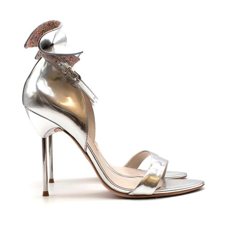 Sophia Webster Silver Leather Crystal Embellished Heels  - Silver metallic leather  - Pink, purple and blue crystal embellished bow detail  - Ankle strap fastening  - Open toe sandals - Stiletto heel   - 105mm heel  - Leather sole and inner sole