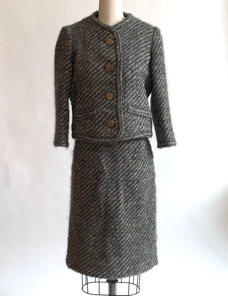 Vintage 1960s Sophie of Saks skirt suit in a super textured grey and white weave. Textured brassy colored metal buttons. Side zip and hook and loop closure at side skirt, five buttons at jacket front..  No content label, feels like it might be a