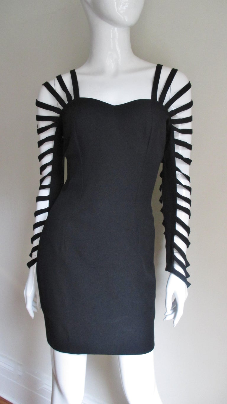 A great little black dress from French designer Sophie Sitbon.  It has a front sweetheart neckline and a low V cut out back.  The shoulder straps consist of bands of fabric emanating from the front top bodice through the sleeves and crossing the