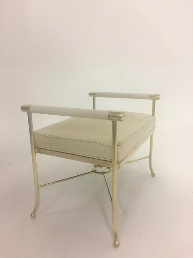 Sexy brass and off white leather bench attributed to Milo Baughman having leather wrapped side handles and pretty neoclassically inspired stretcher connected at the center by a circle.