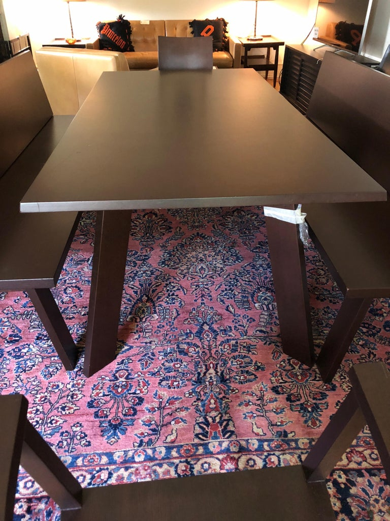 Very modern sleek custom dining table by the German Bulthaup Co., having two matching benches with backs that seat multiple diners along the length of the table. There are also two coordinating armchairs for either end.