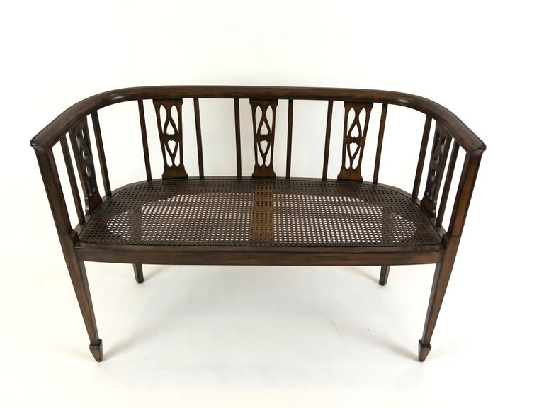 Refined fruitwood settee having lovely curved back with open fretwork, tapered legs and excellent condition caned seat. Custom cushion in a traditional small pattern and neutral color palette is included. Seat height without cushion 17.25.