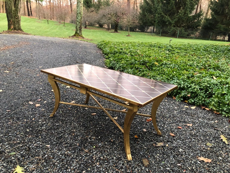 Transitional inlaid wood coffee table by Amy Howard. The table has a banded diamond design with an exotic wood background. Giltwood base has an X-form rope stretcher.