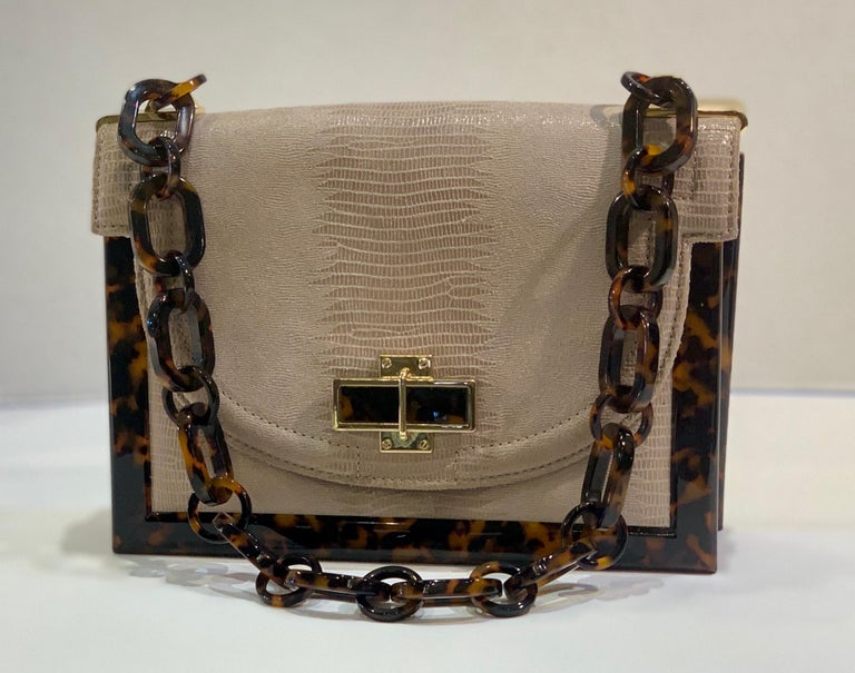 Beautifully textured handbag from American Fashion designer Tory Burch is made of quality pearlized taupe lizard leather with a rectangular, resin tortoise shell frame, chain strap and closure detail.  Bag features a front flap with a magnetic