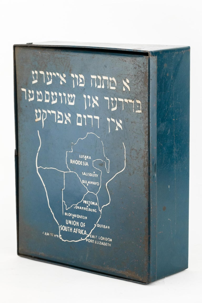 Metal school supply box sent by the South Africa Jewish Wars Appeal to the Wels displaced persons (DP) camp in Austria, 1947. Painted blue with white inscription and map of South Africa, and Hebrew inscription a gift from your brothers and sisters